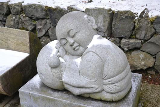 Cute snow covered sleeping monk statue in Koya san