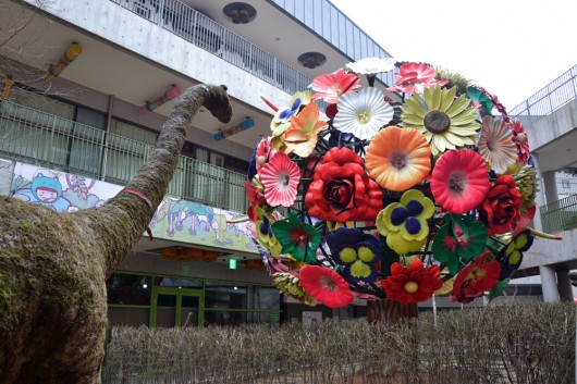 "Giant flowerball and dinosaur amids the ""I like Dalki"" buildings"