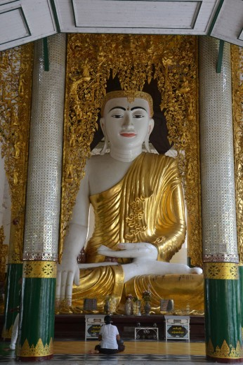 Woman resting in front of an enormous Buddhist statue