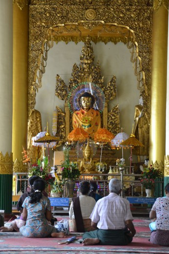 People praying in front of one of the many statues in Shwedagon Paya