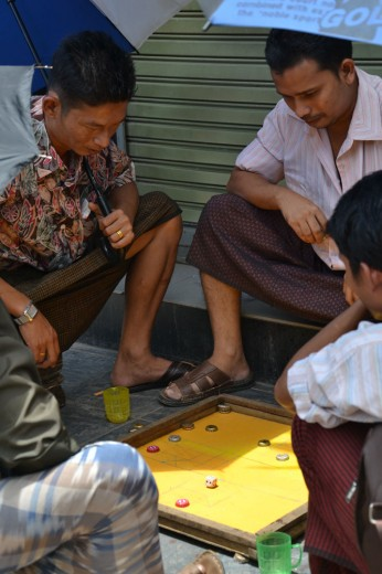 Local merchants playing a boardgame on the street with bottle caps