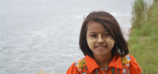 Little girl with Thanaka on her face, yellow white cosmetic paste made from bark