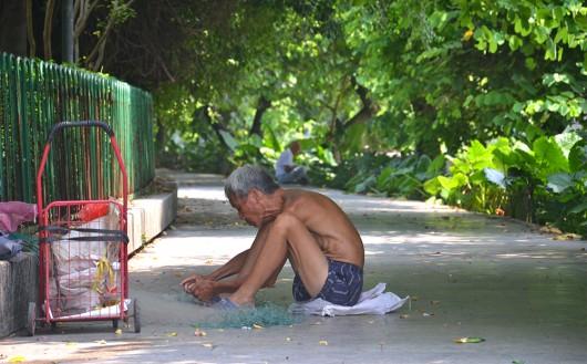 Elder fisherman fixing fishing nets