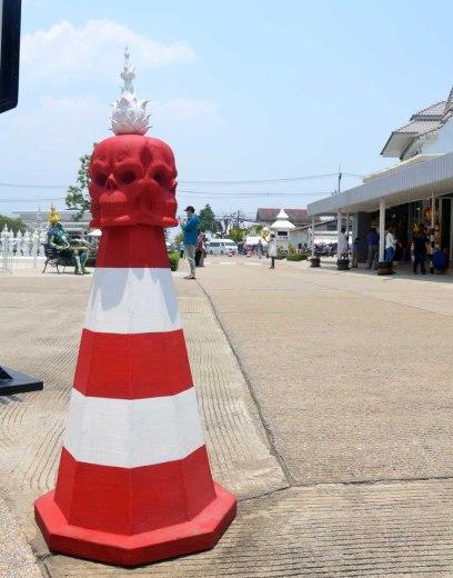 Asian backpacker - Chiang Rai white temple traffic cone